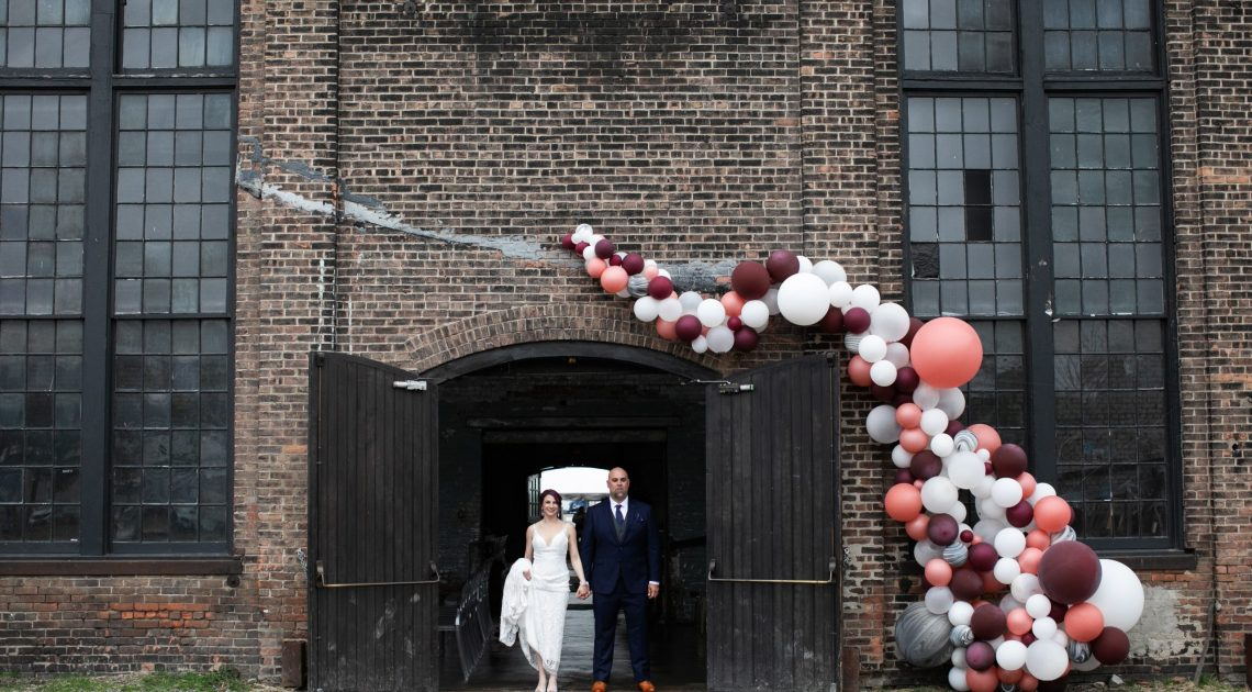 Couple posing in Basilica Hudson doorway with ballon arch