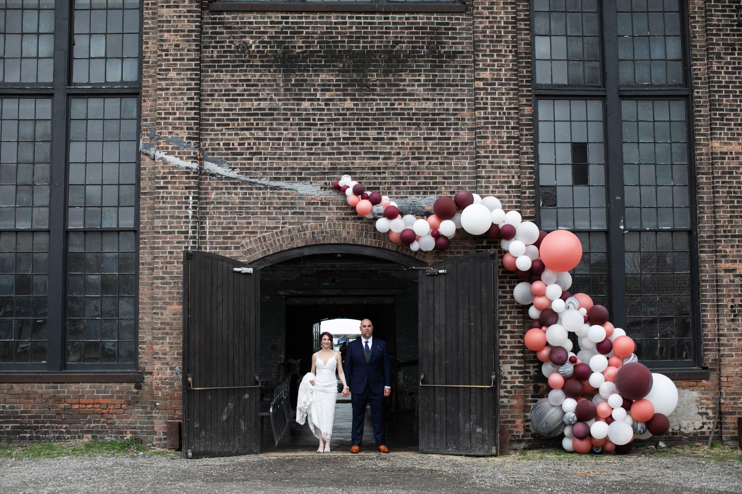 Couple posing in Basilica Hudson doorway with ballon arch