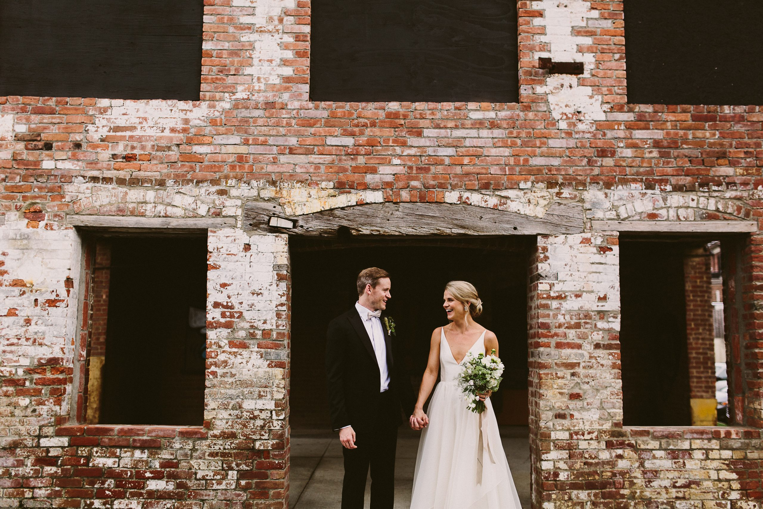 Couple smiling in front of brick building